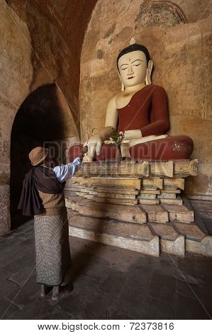 Burmese Man Brings Religious Offerings To Buddha Statue. Bagan, Myanmar (Burma)