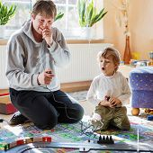 Father and son playing with racing cars on racetrack indoors together poster