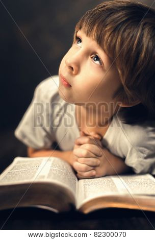 little boy studying the scriptures. poster