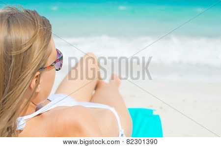 Young Woman Sunbathing On Tropical Beach.