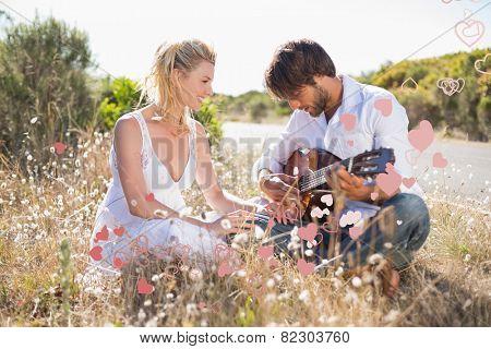 Handsome man serenading his girlfriend with guitar against valentines heart design