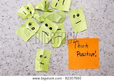 concept for a positive attitude with small crumbled up sad faces and a note with the phrase think positive poster