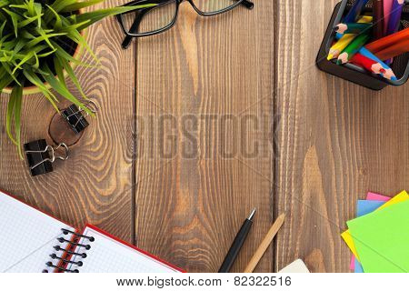 Office table with flower, blank notepad and supplies. View from above with copy space