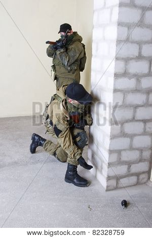 insurgents with AK 47 throws a grenade inside the building poster