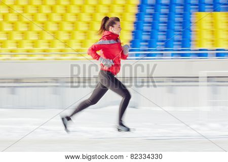 Fit young woman in activewear running at stadium