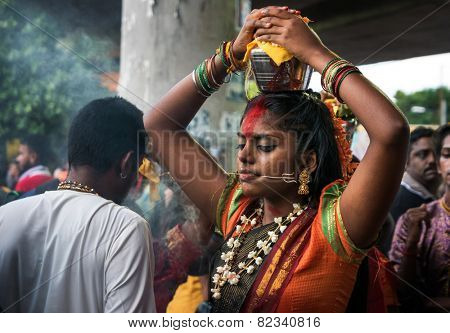 KUALA LUMPUR, MALAYSIA - FEBRUARY 3, 2015: A Hindu devotee places a milk pot on her head to begin walking in a procession to the Batu Caves temple on Thaipusam day, a day of thanksgiving and devotion.