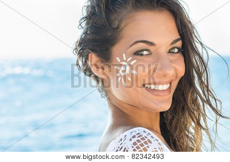 Closeup Of Smiling Young Woman With Suncream On Face At Sea