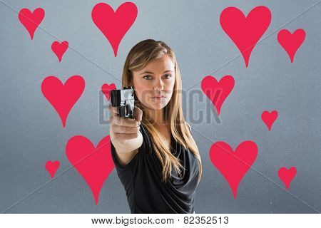 Femme fatale pointing gun at camera against grey