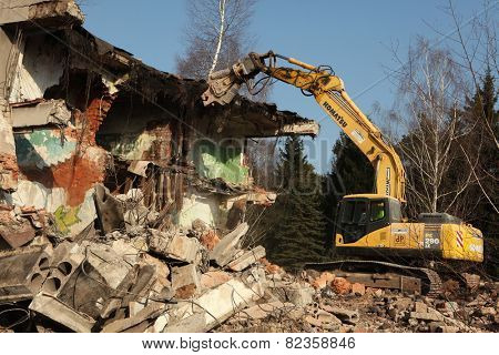 MILOVICE, CZECH REPUBLIC - FEBRUARY 25, 2014: Demolition excavator destroys abandoned buildings in the area of the former Soviet military base in Milovice, some 40 km from Prague, Czech Republic.