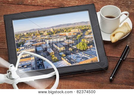 drone aerial photography concept - reviewing aerial pictures of Fort Collins downtown on a digital tablet with a drone rotor and cup of coffee poster