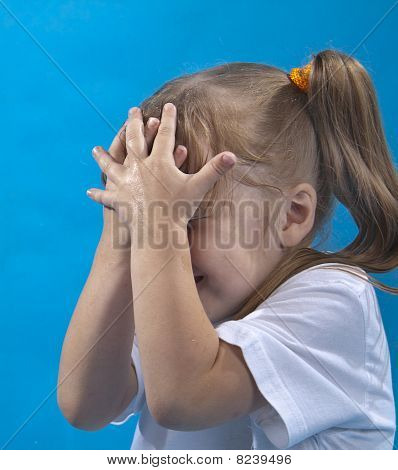 Small Girl Is Covering Her Face By Hands Isolated On Blue