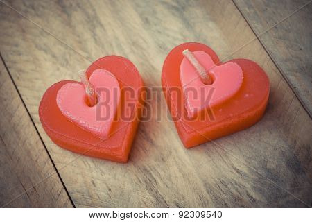 two red scented candles with shapes of a heart on wood plank floor
