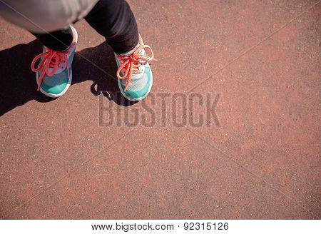 Little girl with sneakers and leggins outdoors
