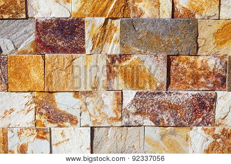 Texture wall pattern with bricks in different tones of ocre, white, grey and brown.