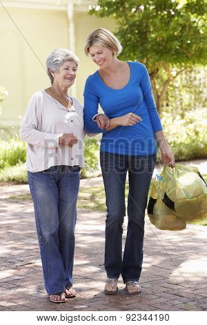 Woman Helping Senior Female With Shopping