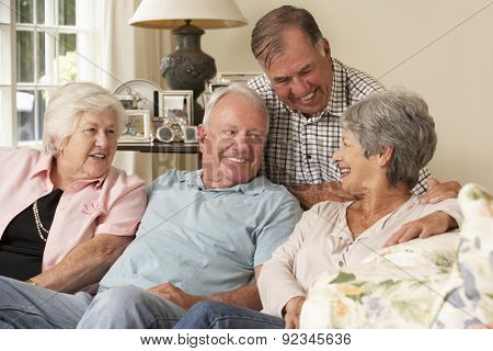 Group Of Retired Friends Sitting On Sofa At Home Together poster