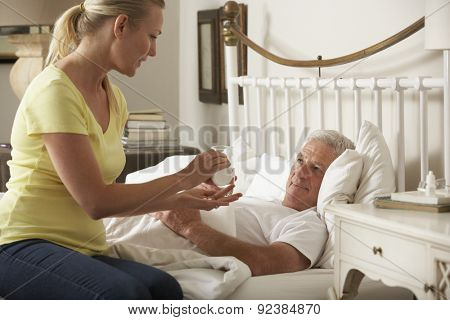 Adult Daughter Giving Senior Male Parent Medication In Bed At Home