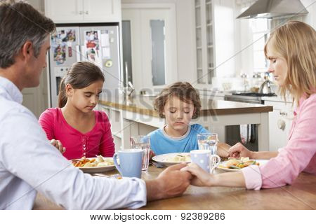 Family Praying Before Having Meal In Kitchen Together