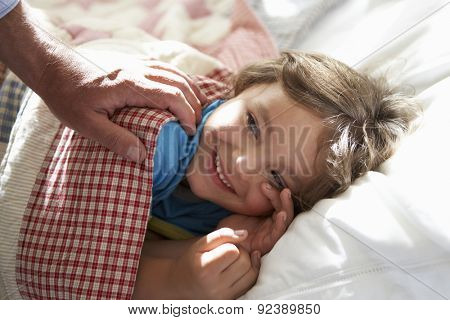 Parent Waking Young Boy Asleep In Bed