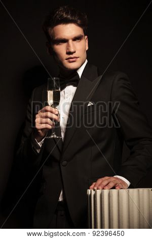 Handsome elegant business man holding a glass on champagne in his hand while leaning his hand on a white column.