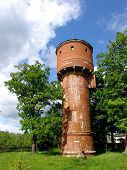 an ancient brick water tower with trees around and blue sky poster