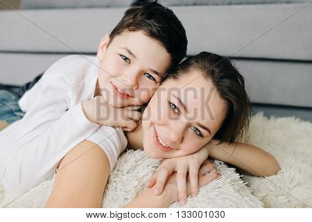 Beautiful brother and sister lying quietly on the floor close embraces emotions