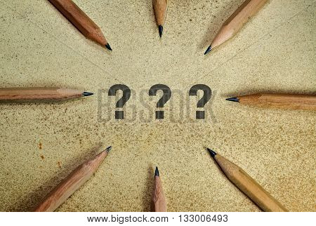 Three question marks surrounded with pencils on grunge background