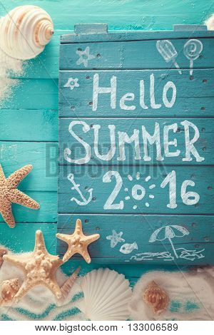 Summer background. Wooden sign with Hello Summer lettering. Summer beach. Wooden background with white sand and seashells.Shells starfish and sand. Holiday background