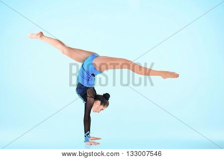 The girl doing gymnastics dance on a gray background
