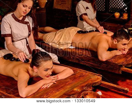 Young family having stone massage. Ayurveda lastone spa massage treatment.