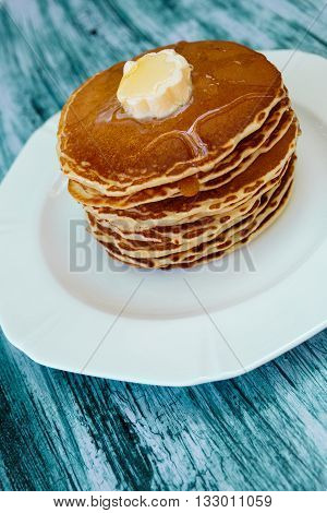 Pancakes with butter and honey on white plate on blue wooden background. Stack of wheat golden pancakes or pancake cake closeup.
