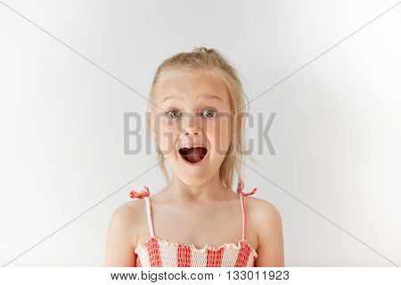 Little European Girl Opening Mouth In Surprise And Raising Her Eyebrows With Wonder. Blond Child Wit