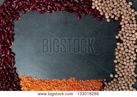 Frame made from Group of beans over black background with copy space. Group of beans lentils and chick-pea on black background.