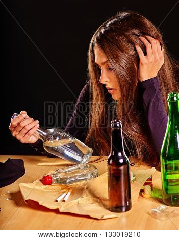 Girl in depression drinking alcohol and smokes cigarettes in solitude. Alcohol problems.