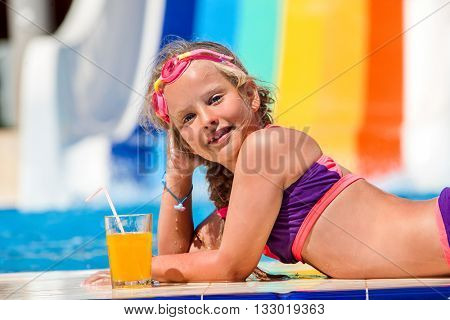 Child on water slide at aquapark drinking cold squeezed orange juice. Children lie on edge of swimming pool. Summer swimming holiday.Outdoor.
