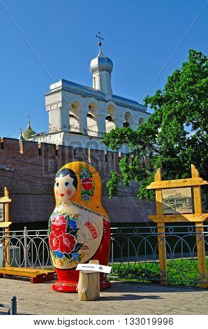 VELIKY NOVGOROD RUSSIA -JUNE 3 2016. Belfry of St Sophia cathedral with big colorful Russian doll matrioshka on the foreground in Veliky Novgorod Russia