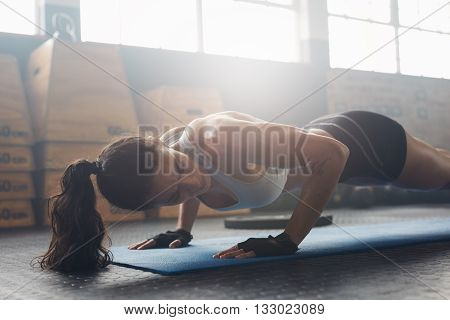 Female Exercising On Fitness Mat At Gym