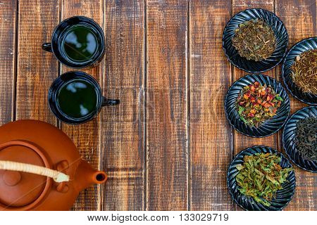 Different kinds of tea on plates near brown teapot and two cups with tea on wooden background. Assortment of dry tea. Tea concept. Tea leaves. Copy space