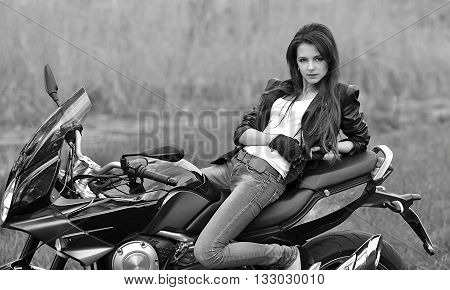 Biker girl, sexy biker girl with bike, motorbike, motorcycle, beautiful, serious, attractive, audacious, daring, nice, fashionable, posing girl, rider, adult, biker, single biker powerful girl. Black and white photo.