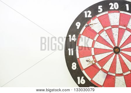 Two old darts on an old dart board with many holes. Concept of competition; failed attempt (missed target); no skill; or no improvement. White background and copy space on the left.
