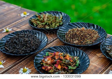 Different kinds of tea on black plates on wooden table with flowers of chamomile in garden and on nature background. Assortment of dry tea. Tea concept. Tea leaves. Closeup