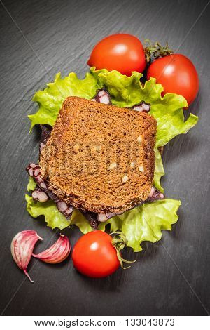sandwich with sausage and vegetable on a dark background