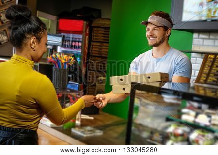 Customer takes his order in a pizzeria.