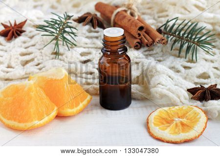 Natural aromatherapy. Citrus orange scent, cinnamon,anise, pine scent. Holiday aromatherapy recipe, mood-lifting energy booster.  Essential oil bottle, knitted blanket.