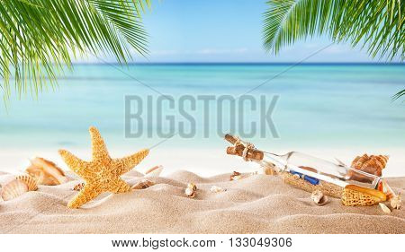 Tropical beach with various shells and glass bottle with message in sand, copyspace for text. Concept of summer relaxation