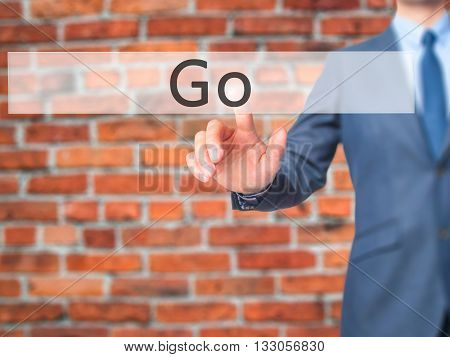 Go - Businessman Hand Pressing Button On Touch Screen Interface.