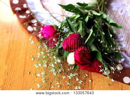 unblown bouquet of purple peony on wooden table
