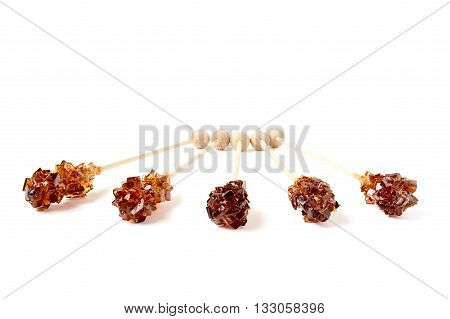 Five brown sugar stirrers isolated on white.