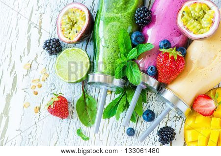 Berry and fruit smoothie in bottles healthy summer detox yogurt drink diet or vegan food concept fresh vitamins mango lime