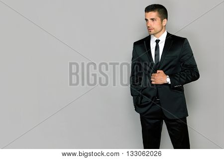 guy in a suit on a gray background young male model in a black suit and tie